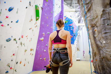 Photo from back of young female athlete on background of wall for rock climbing