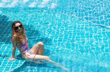 Young woman relaxing in swimming pool in summer