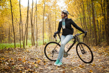 Picture of girl in helmet, jeans next to bicycle in autumn park