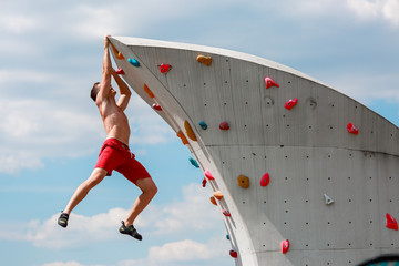 Photo of young sporty brunet in red shorts hanging on wall for rock climbing against blue sky with clouds