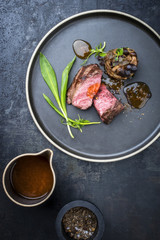 Traditional Italian barbecue aged sliced fillet steak with wild garlic and pioppinos as top view on a plate