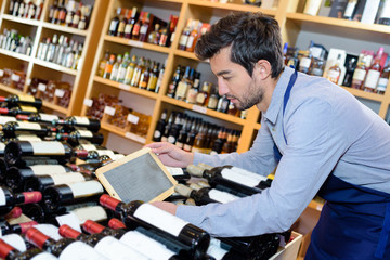 young handsome wine store seller holding tablet