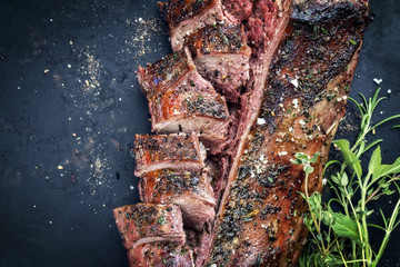 Traditional barbecue aged saddle of venison marinated as top view on an old rustic board with copy space left