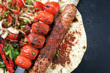 Traditional Adana Kebap skewer with tomato and salad on a flatbread with copy space right