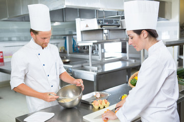 Male and female chefs prepping