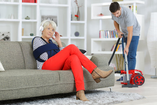 young man home help cleaning ladys living room