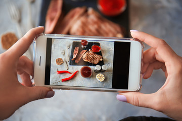 Woman taking photo of barbecue sauce and grilled meat with mobile phone