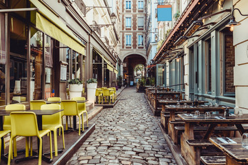 Cozy street near Boulevard San-German with tables of cafe and pub  in Paris, France
