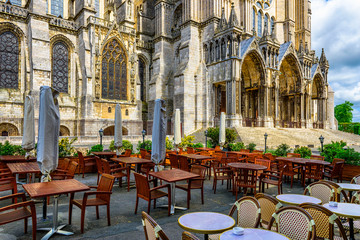 Wall Mural - Old street with Chartres Cathedral and tables of cafe in a small town Chartres, France