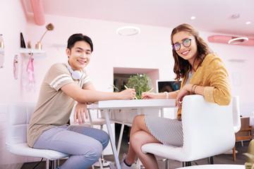 International exam. Young couple of beaming smart postgraduates preparing for international exam