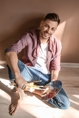 Male artist with paint tools and palette on floor near color wall