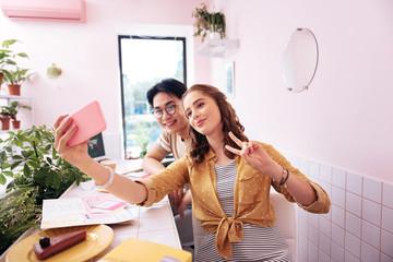 Making selfie. Two modern good-looking students making really memorable selfie in coffee room