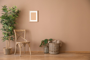 Obraz Wooden chair with wicker basket and plant near color wall - fototapety do salonu