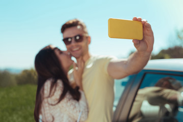 Yellow smart phone. Smiling handsome man holding his yellow smart phone while making memorable photo with his woman