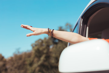 Dress and bracelets. Woman wearing orange dress and accessories taking hand out of window during her travel