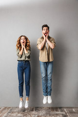 Full length portrait of a shocked young couple jumping