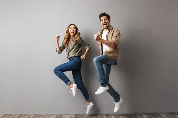 Full length portrait of a cheerful young couple jumping