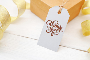 Mockup gift and blank tag with calligraphic text Thank you on white wooden background with gold ribbon. Lettering Thanksgiving Day