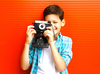 Portrait happy little boy teenager with retro camera on red background