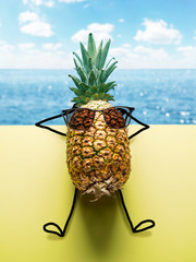 Pineapple man in sun glasses on blue-and-yellow background.