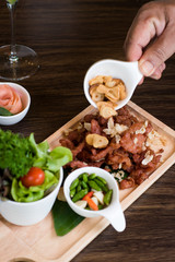 Fried Pork with Garlic. Deep Fried Crispy Pork Belly Cooked with Garlic and spicy dipping sauce on wooden table background