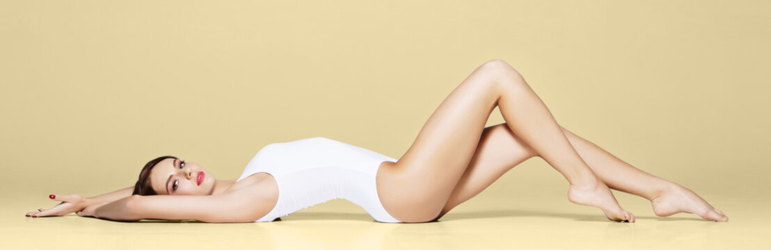 Young, beautiful and sporty girl in white swimsuit. Model posing in studio.