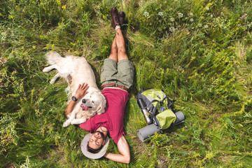 top view of tourist and golden retriever dog lying on green grass with backpack