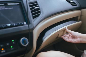 Hand open glove compartment box inside modern car