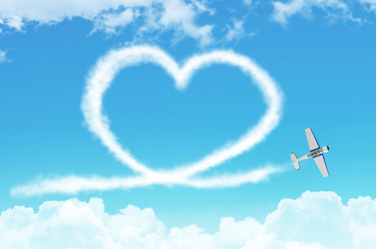 Love figurative heart from a white smoke trail light-engine airplane among the clouds.