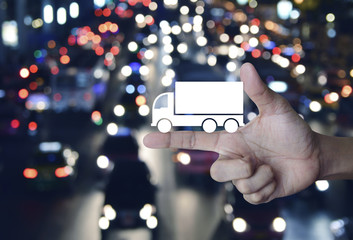 Truck flat icon on finger over blur colorful night light city with cars, Business truck transportation service concept