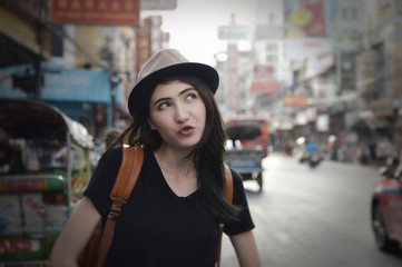 Young asian happy woman traveler with a backpack on her shoulder and travel hat standing over China town, Bangkok, Thailand, Travel holiday relaxation concept