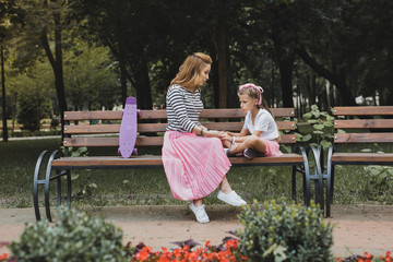 Fashionable mother. Fashionable mother wearing long pink skirt sitting on bench in the park near her daughter