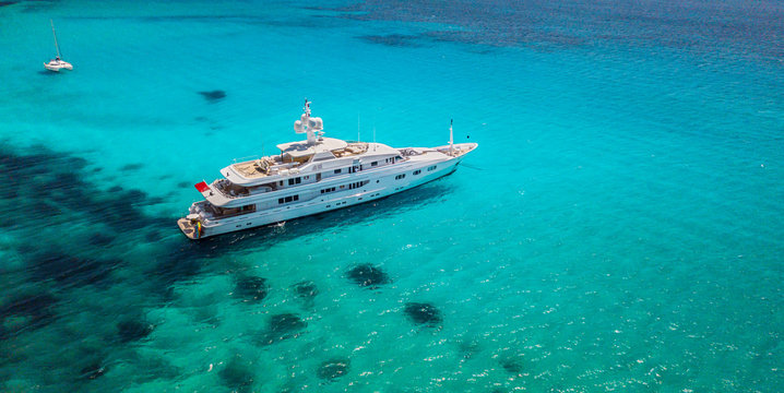 Big luxury yacht anchoring in shallow water,