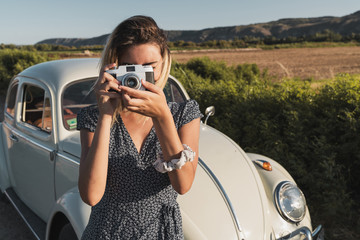 Stylish woman in countryside with photo camera