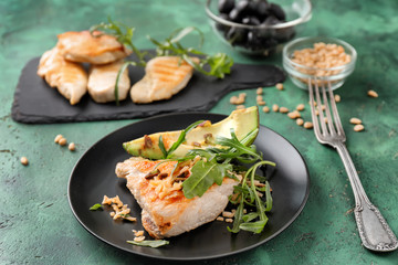 Plate with tasty grilled chicken fillet and ripe avocado on table