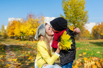 Mother and boy walking in autumn park. The child gently hugs and kisses mom.