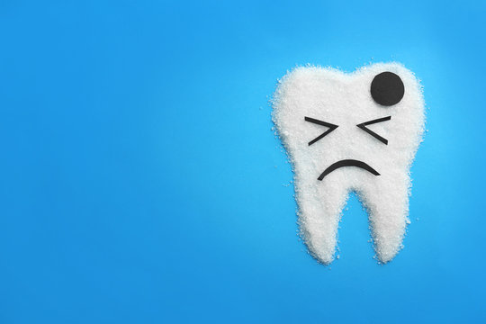 Molar tooth made of sugar on color background. Healthy teeth concept