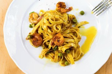 Tagliatelle with shrimps and pea on plate.