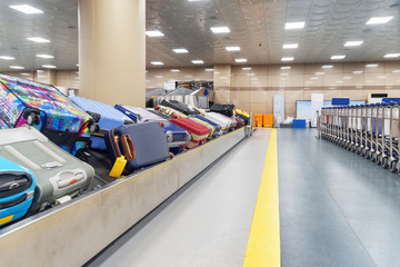 Suitcases on luggage conveyor belt and row of trolleys