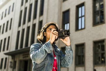 Woman with retro camera in the city