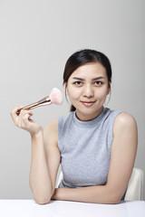 Beautiful young woman cosmetic powder
