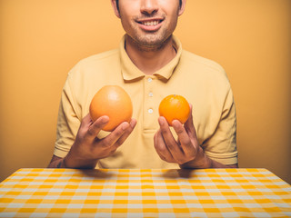 Young man comparing orange with grapefruit