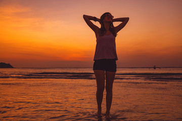Silhouette of a girl in sunset / sunrise time over the ocean.