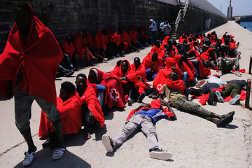 Migrants rest after arriving on a rescue boat at the port of Tarifa