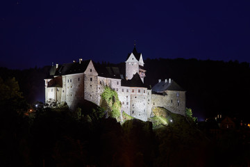 Night view on Loket Castle ( Hrad Loket, Burg Elbogen ) impregnable,12th-century Gothic style castle on a massive rock with illuminated  thick walls. Tourist spot near to Karlovy vary, Czechia.