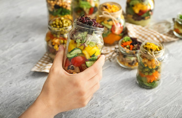 Woman holding mason jar with vegetable salad