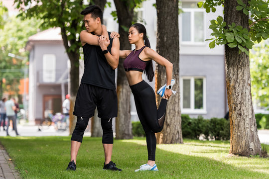 young asian sportsman and sportswoman stretching on grass in park