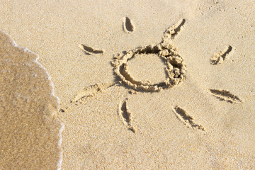 sun drawn on the sandy beach in resort on summer vacation rest. The symbol of the sun drawing on the sand. Background close up.