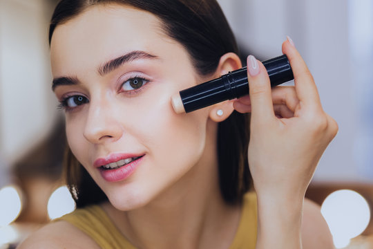 Concealer stick. Charming beautiful woman using concealer stick while putting makeup on
