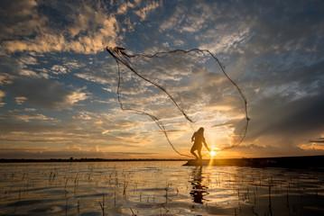 fisherman cast a net at lake in the moring time , silhouette light